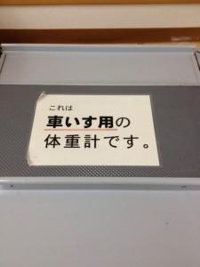 車いす用体重計の中央には、A4晩の紙が貼ってあり、いす用の体重計です。と、記載しています。