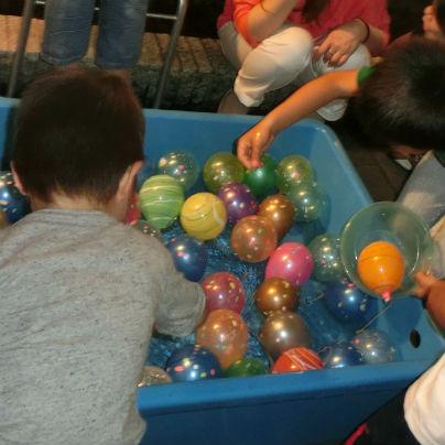 水色のFRP製水槽の中にたくさんのボールが入っていて、数人の子供らが懸命に取ろうとしています