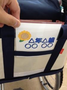 車いす用トートバッグに、名前を書いた札を入れているところ
