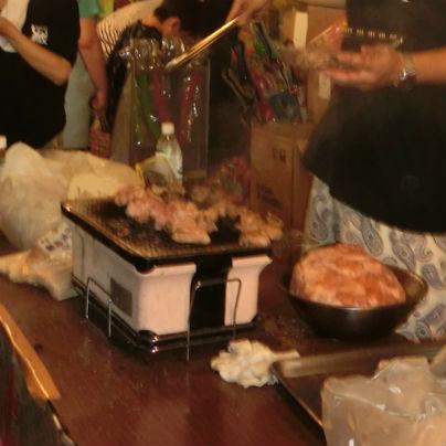 机の上に焼き肉器が置いてあり、若い男性が調理しています。