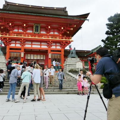 伏見稲荷大社で記念撮影をする男性の観光客。三脚にカメラを固定して撮影しています。