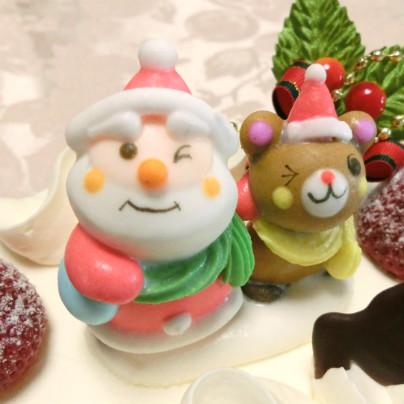 ムッシュマキノのクリスマスケーキの上では、サンタクロースと小熊が並んで見上げながらウィンクしています。