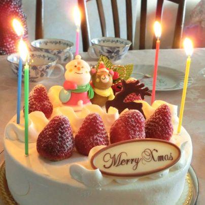 テーブルの上には白いクリスマスケーキ、苺が前に4つ、その奥に2つ、苺のあいだでサンタクロースと熊の人形が乗っています。