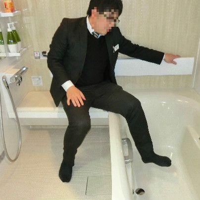 右側に浴槽、左側に洗い場。移乗ベンチに腰掛けて片足づつ浴槽につかってゆく様子。