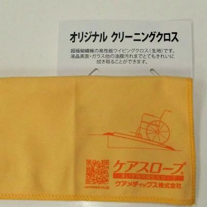 オレンジ色の布にケアメディックス、車椅子用可搬型スロープ、ケアメディックス株式会社とQRコードが書いています
