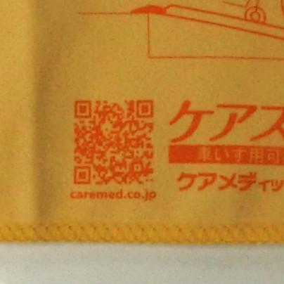 オレンジ色の布に、濃いオレンジ色でケアメディックスさんのQRコードに caremed.co.jp と言う文字