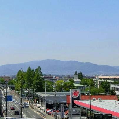 手前に出光のガソリンスタンド、その向こうには雲ひとつ無い晴天の下で青みがかった山が写っています。