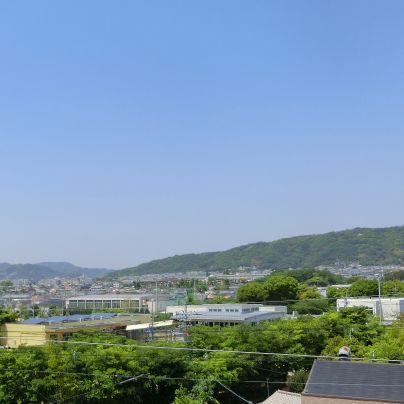雲ひとつない青空のもとに緑に覆われた五月山