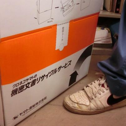 段ボール箱を床の上においてます。上半分はオレンジ色の段ボール箱、下半分の白い部分に黒い文字でクロネコヤマトの機密文書リサイクルサービスと書いてあります。