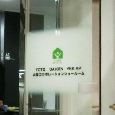 透明なガラス扉で、顔のあたりは横幅一杯、たかさは50センチほど白く縫ってあり、緑のマークと 、TOTO DAIKEN YKK ap 大阪コラボショールーム と黒い文字で書いてあります。