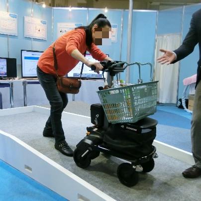 い電動歩行アシストカートを押して高齢の女性が坂を下りています。