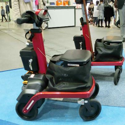 青い床の上に赤色の電動歩行アシストカート『ロボットアシストウォーカー RT.1』が二台置いてあります。