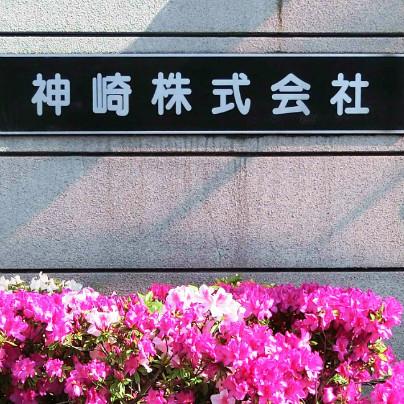 グレーの壁に黒い背景で「神崎株式会社」と記した銘板。その下には赤やピンクのつつじがたくさん咲いています。