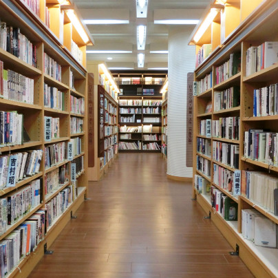 箕面中央図書館は、木製の床、木製の棚が左右と奥にたっていて多くの書物が収納されています。