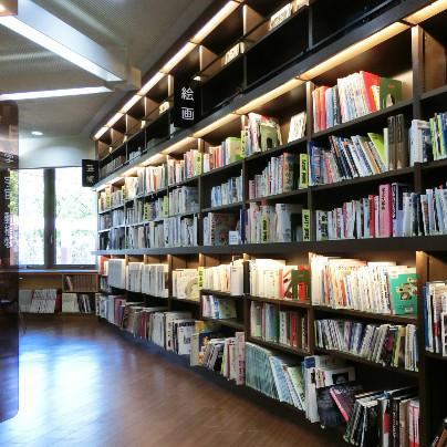 箕面中央図書館で左奥に大きな窓、右側に木製の棚とたくさんの書物
