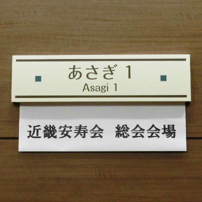 茶色の壁に、白いプレートで「あさぎ1 近畿安寿会 総会会場」と書いてあります