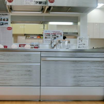 新型のシステムキッチンが真っ正面に1台、ステンレスで木目を再現したステンレスパネルを備えています。