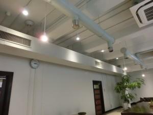白い壁に褐色の木製扉、天井は梁が無く配管が剥き出しです。