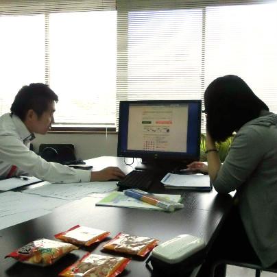 黒い机のうえに横長の大きなモニターが一台。左側に若い男性、右側に若い女性が座って話ししています。