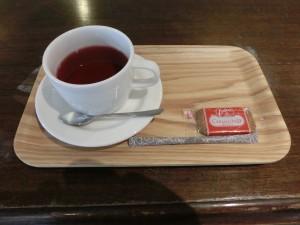 木目の机の上に木目のお盆、白いティーカップに薄赤色のハーブティーが入っています