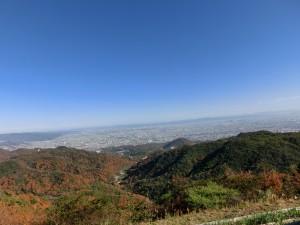 青空のしたで、標高500メーターくらいの場所から三田市の町並みを見ています。左側の山複に紅い木々が葉が映っています。