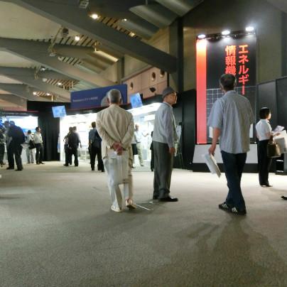 新商品内覧会場で壁並んでに展示物が あり、その前には数人のひとが見てるとなしに立っています。
