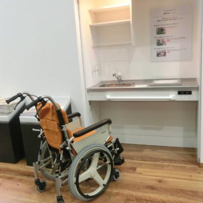 車いす対応のキッチンが奥に手前には車いすが一台。