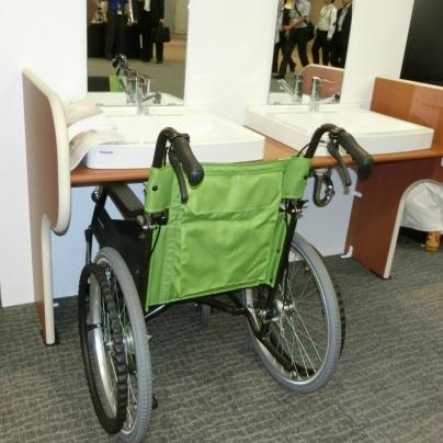 洗面台は浅く、膝が入るよな構造です。そのボウルの前には緑色の車いすが置いてあります。