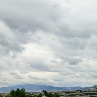 写真の下側に町並みと山、空は雲で覆われています。