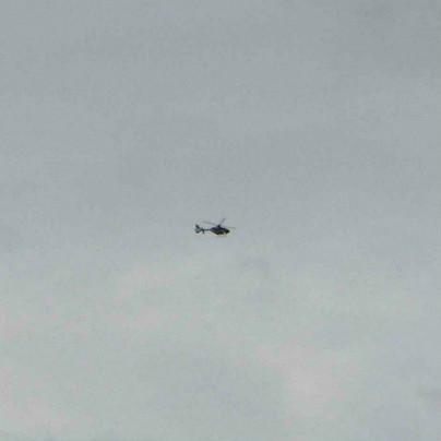 曇り空を背景に左から右に向かってヘリコプターが1機、飛んでいます。