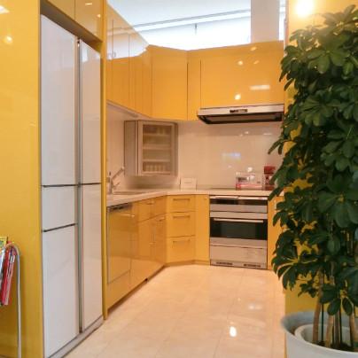 黄色いシステムキッチンがコの字レイアウトで写っています、