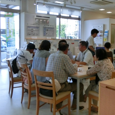 白いYシャツを着た男性が4人のお客様に説明をしています
