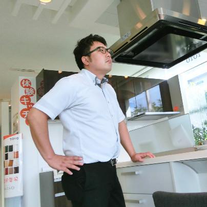 キッチンの天板に手をついて、腰に手をあててる男性