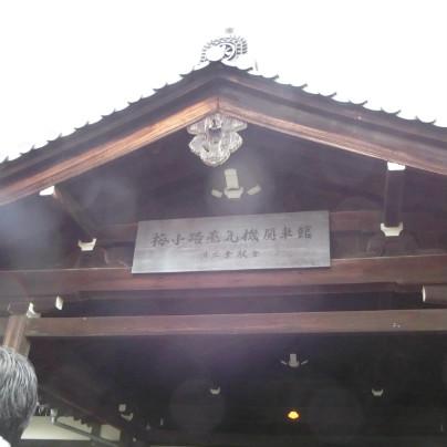 鈍色の瓦、木造の切り妻屋根、看板に梅小路蒸気機関車館と看板を掲げた入り口