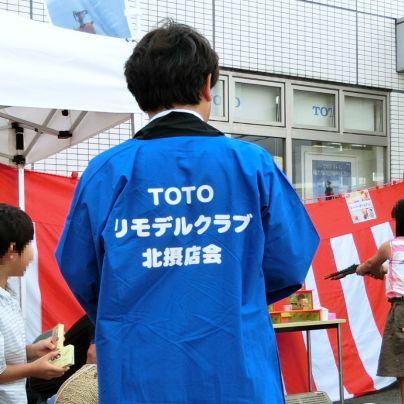 紅白の垂れ幕の前でTOTOリモデルクラブ北摂店会の青い法被を着た会員の後ろ姿が写っています。
