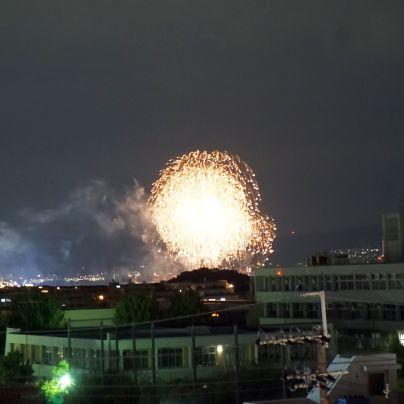 漆黒の夜空の手前に町並み、その奥には先ほどより明るい花火の大輪が咲いています。