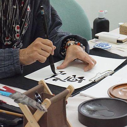 書道家、蓮創明さんによる誕生日の花言葉を書いているところ