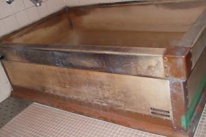 補修前の木製浴槽、右側は銅板が剥がれてきたので、ビニルテープで仮りどめしています。