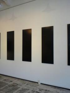 白い壁に幟のような形をした5枚の写真が飾られています。