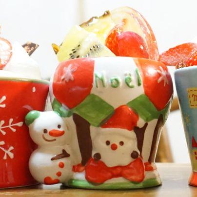 雪だるまが寄り添うサンタクロースのカップに入った洋菓子