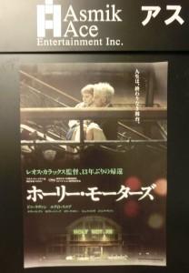 映画、ホーリー・モーターズのポスターが黒い壁に貼ってあります。主演のドニ・ラヴァンが、カイリー・ミノーグを抱えて階段を上がるシーンです。