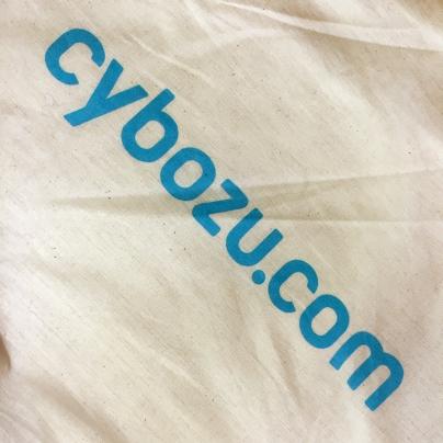 白いキャンバス地の布に、水色の文字で、 cybozu.com と、記されています