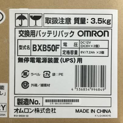 段ボール箱に白地に黒い文字で交換用バッテリパック OMRON BSB50F と、書いてあります。
