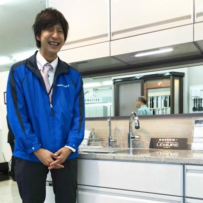 白いシステムキッチン、レミューの前で青いジャンパーを着た若い男性のn営業マンが笑っています