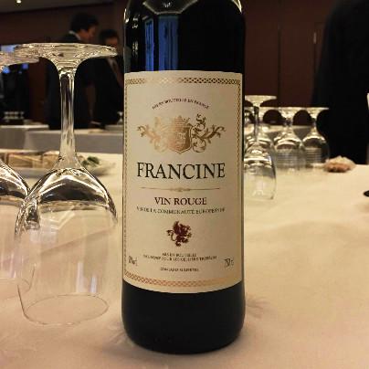 白いテーブルの上に濃褐色のワインボトルが1本。、白いラベルにFRANCINE WIN ROUGEと書いてあります。