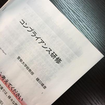 黒い机の上に白いコピー紙に『コンプライアンス研修』と記されたテキストが置いてあります