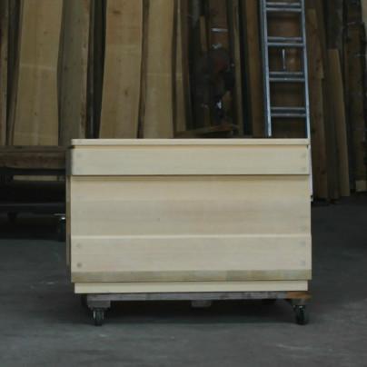 木の板の前に、完成した木製介護浴槽が置いてあります。