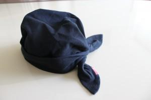 白い机の上に黒い生地のバンダナを帽子の形状にしています。真後ろに大きな結び目があり。