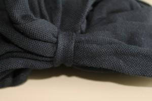 白い机の上に黒い生地のakko バンダナ帽をのせていて、結び目をアップで映しています