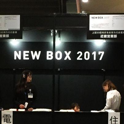 黒字の壁に白い文字でNEW BOX 2017と書いた前で黒い受付机を前に二人の女性が立っています。